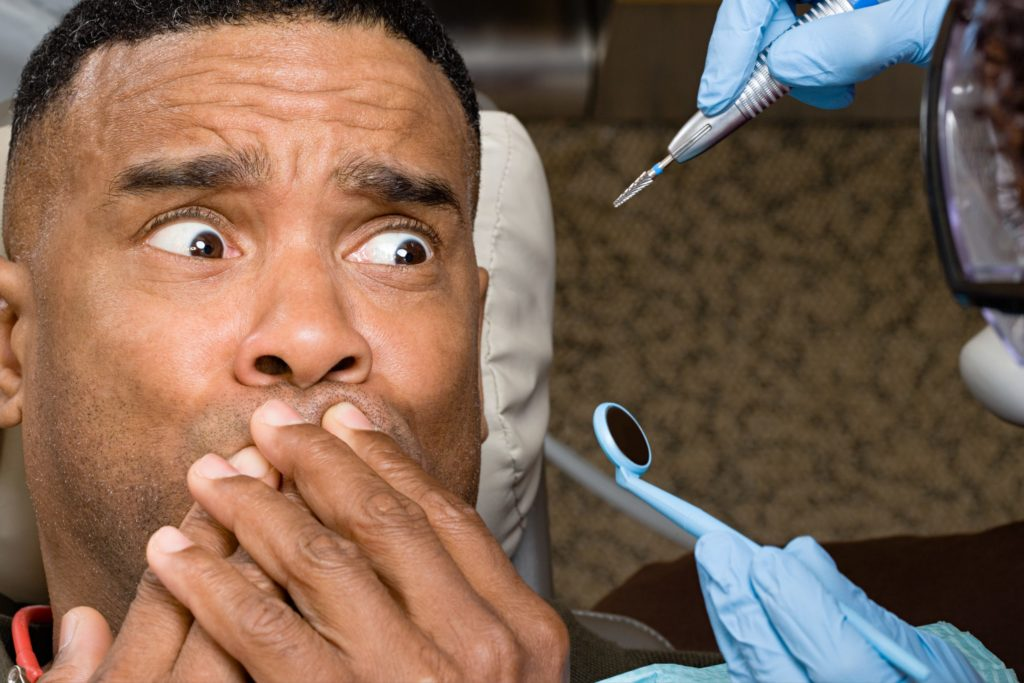 man holding mouth with dental implements near him